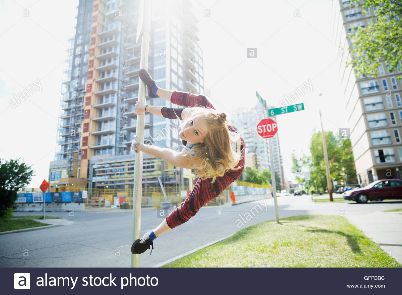 Young woman doing parkour on pole in urban street - Stock Image