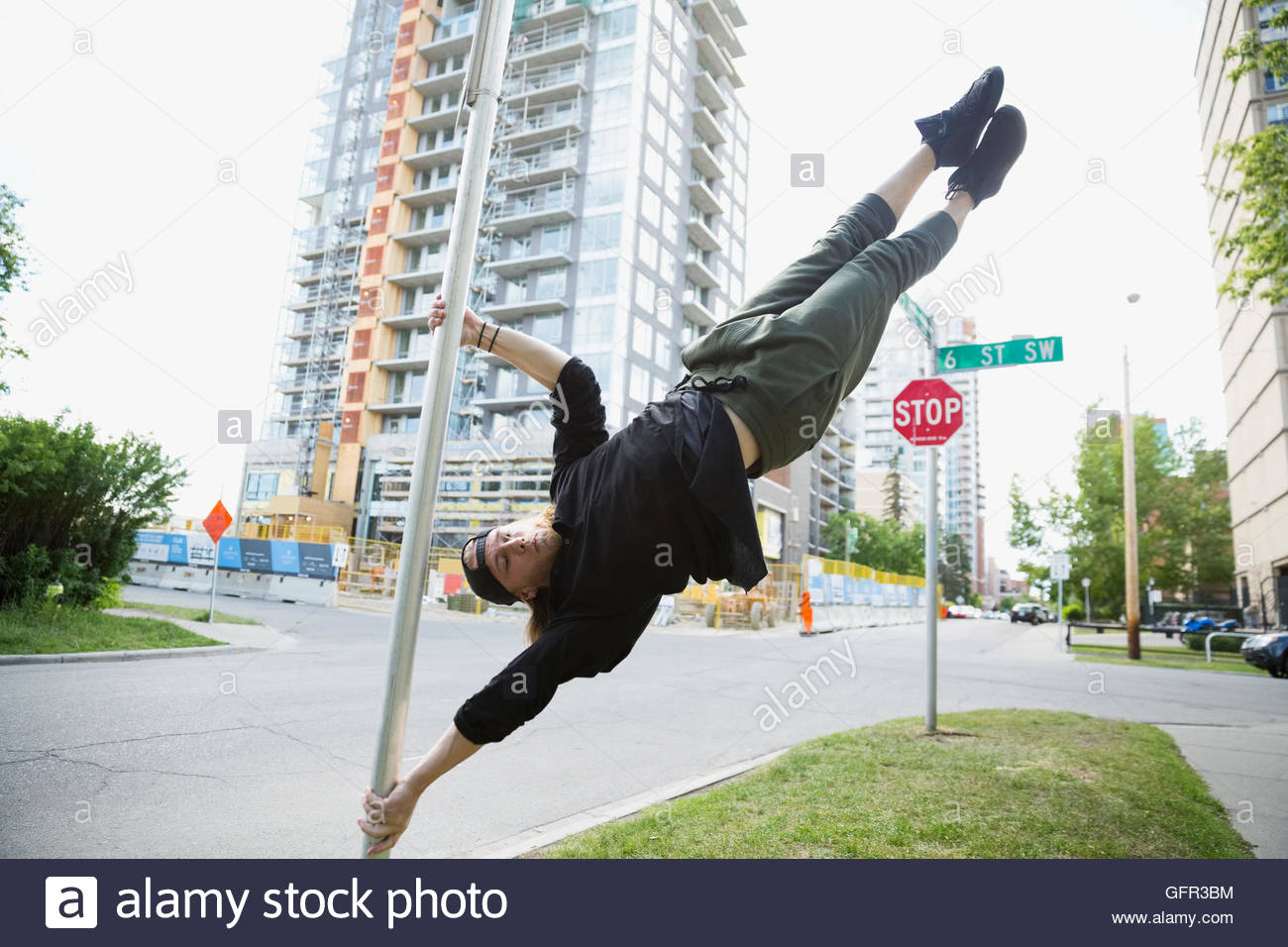 Young man doing parkour on pole in urban street - Stock Image