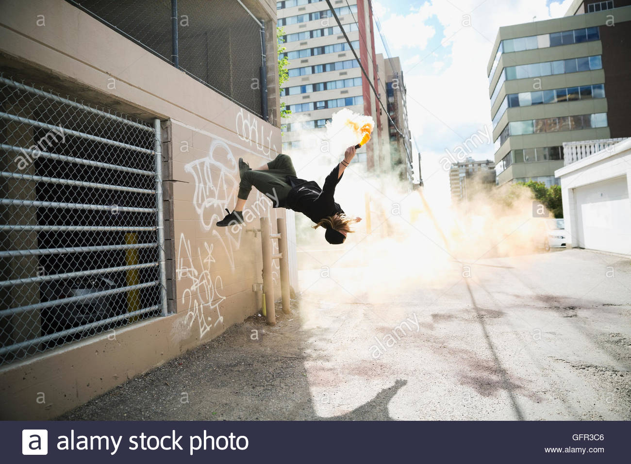 Cool young man doing parkour backflipping with powder cannon in urban alley - Stock Image
