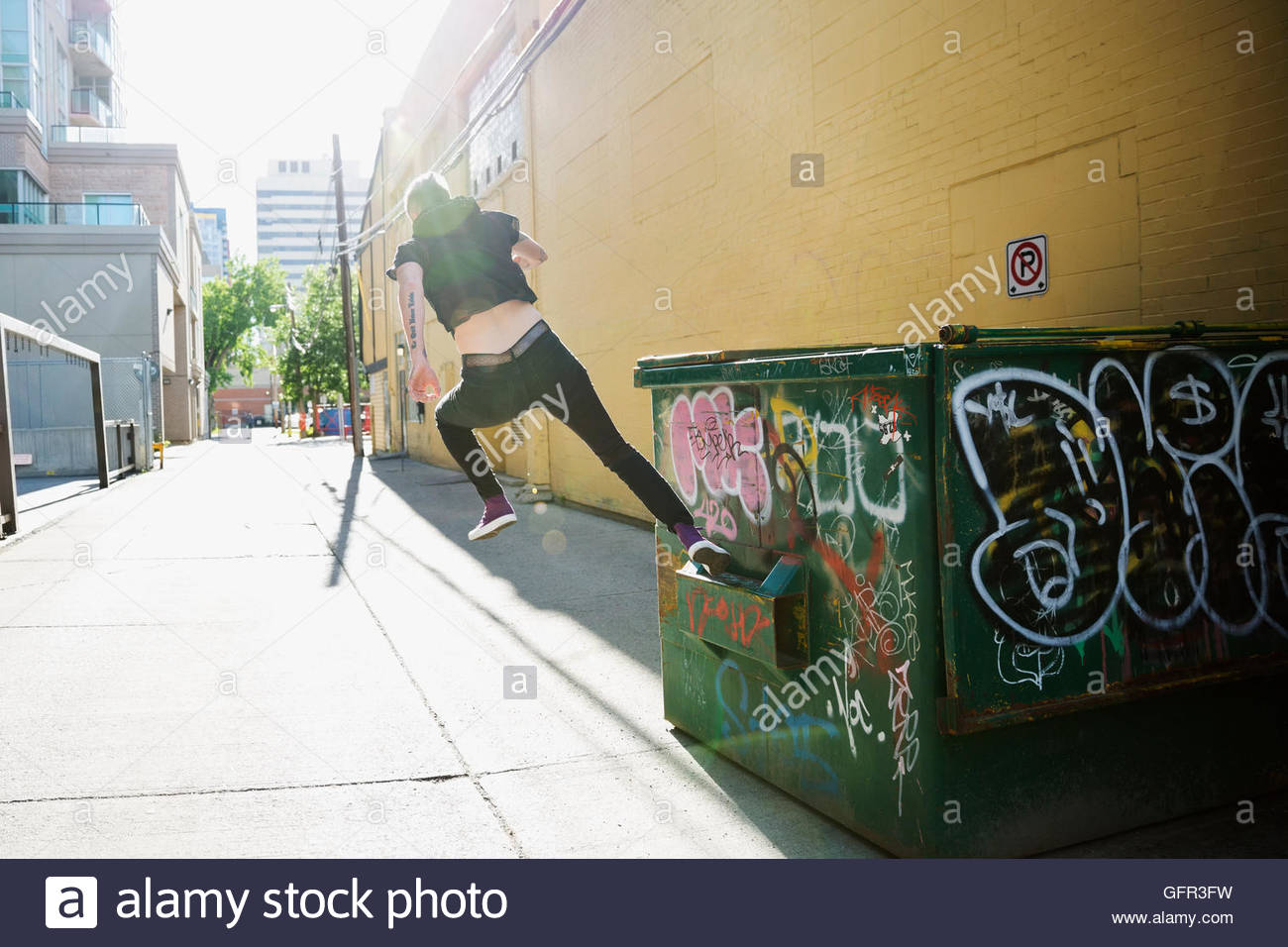 Cool young woman doing parkour at dumpster in sunny urban alley - Stock Image