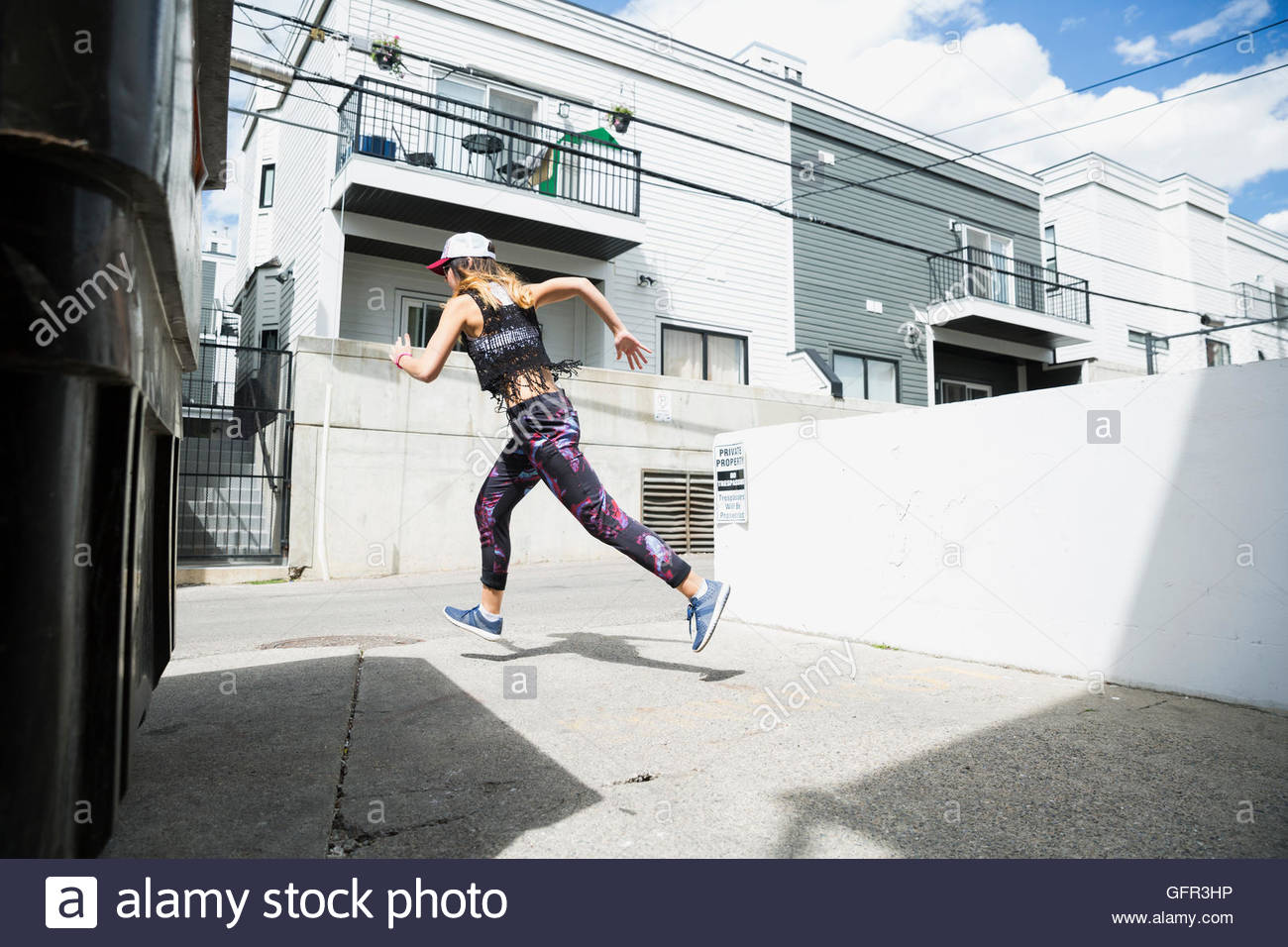 Young woman running in sunny urban alley - Stock Image