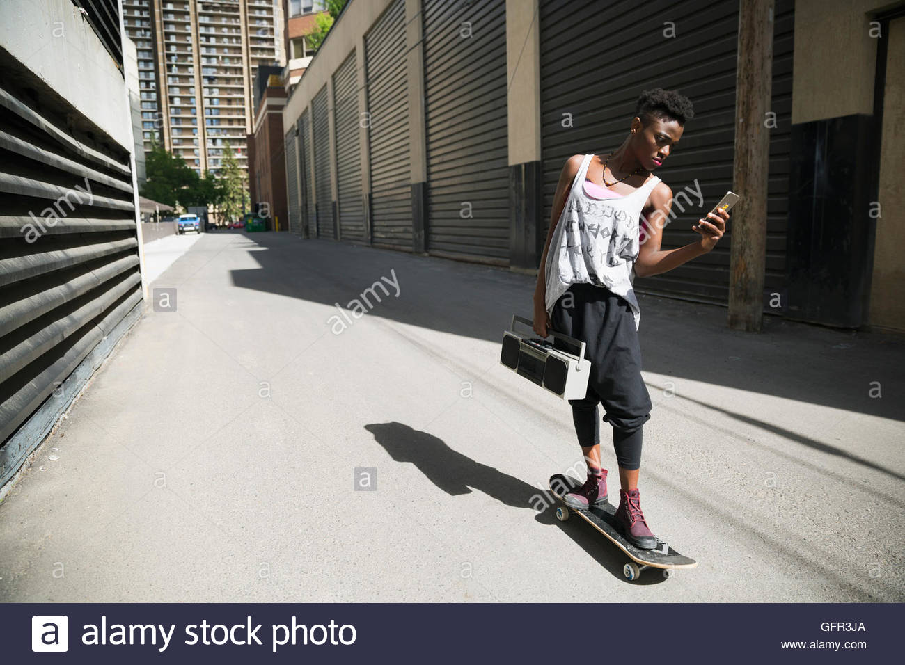 Cool young woman skateboarding with boom box and texting in urban alley - Stock Image