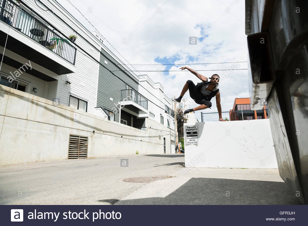 Young man doing parkour free running in sunny urban alley - Stock Image