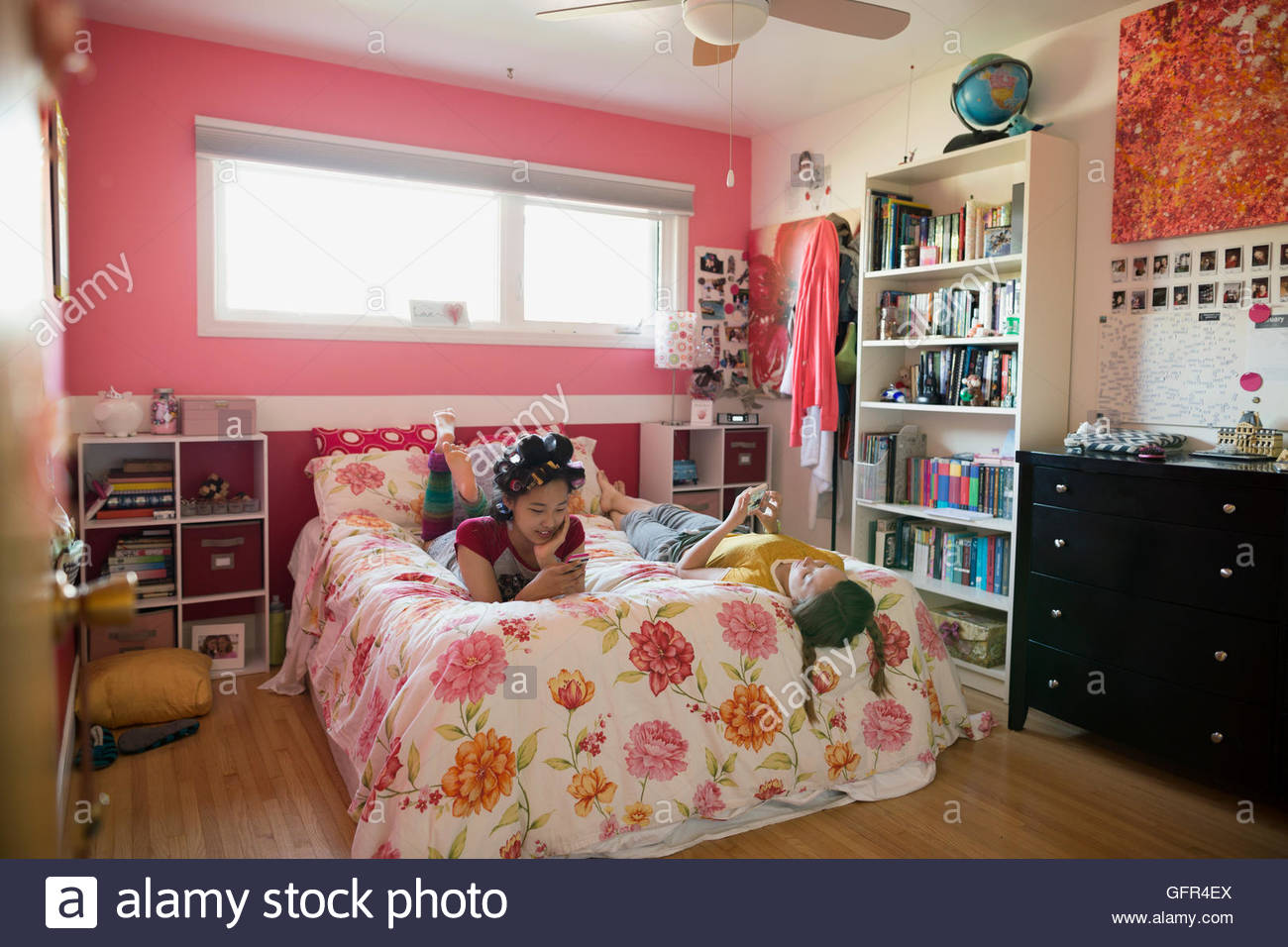Girls looking at cell phones on bed - Stock Image