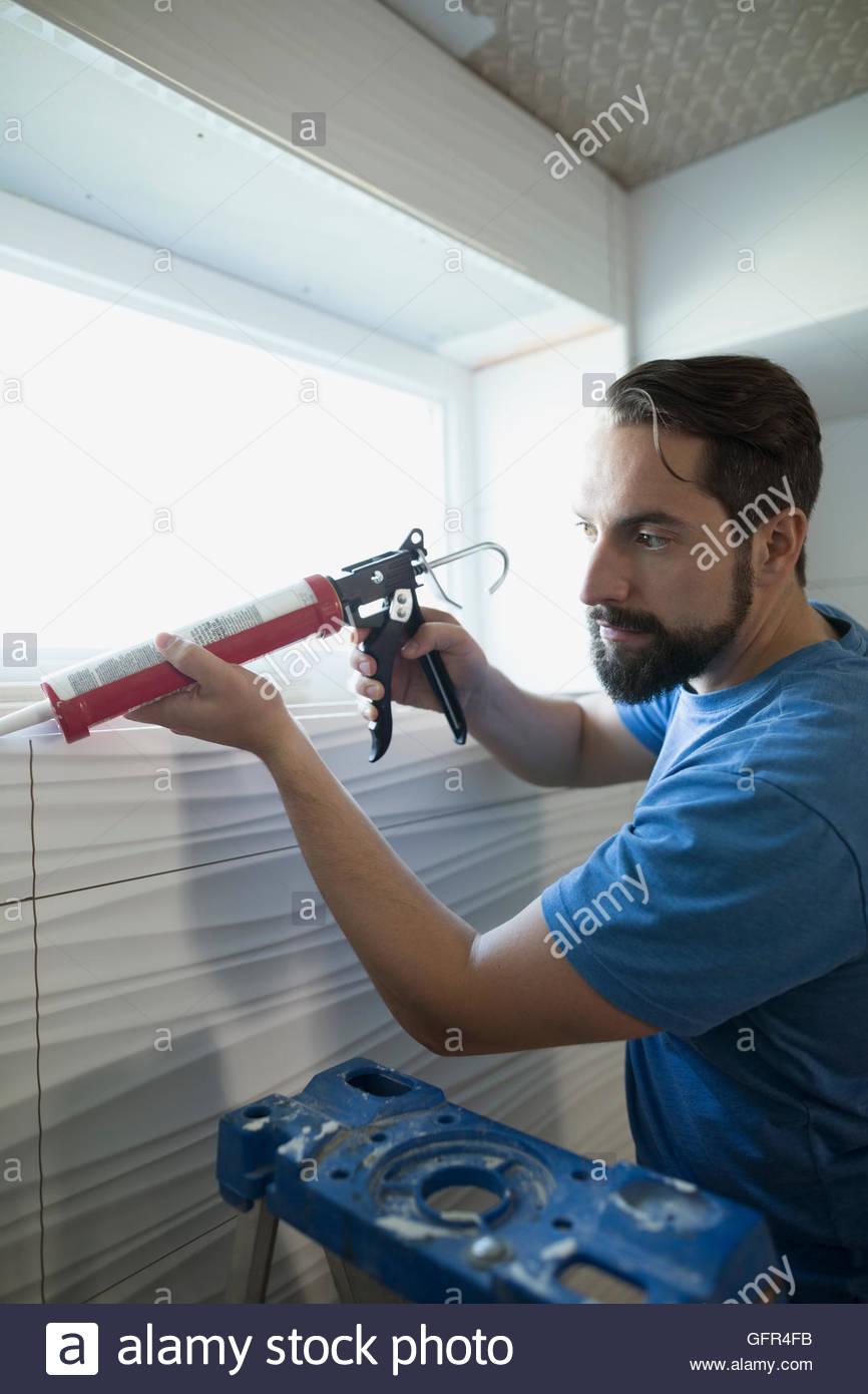 Man using caulk gun for home improvement project - Stock Image