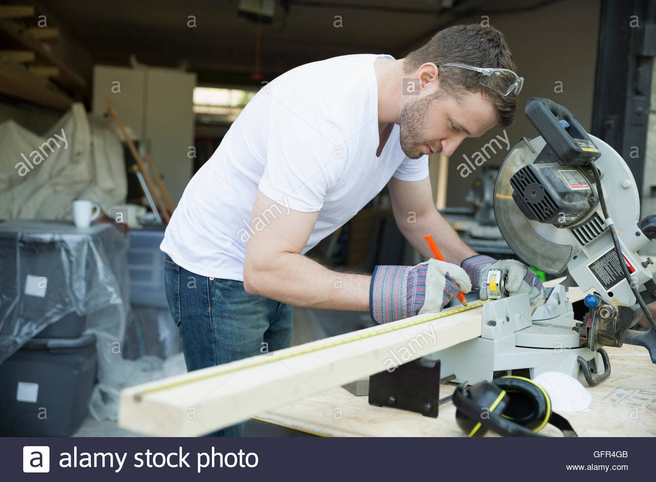 Man marking wood for home improvement project at table saw in driveway - Stock Image