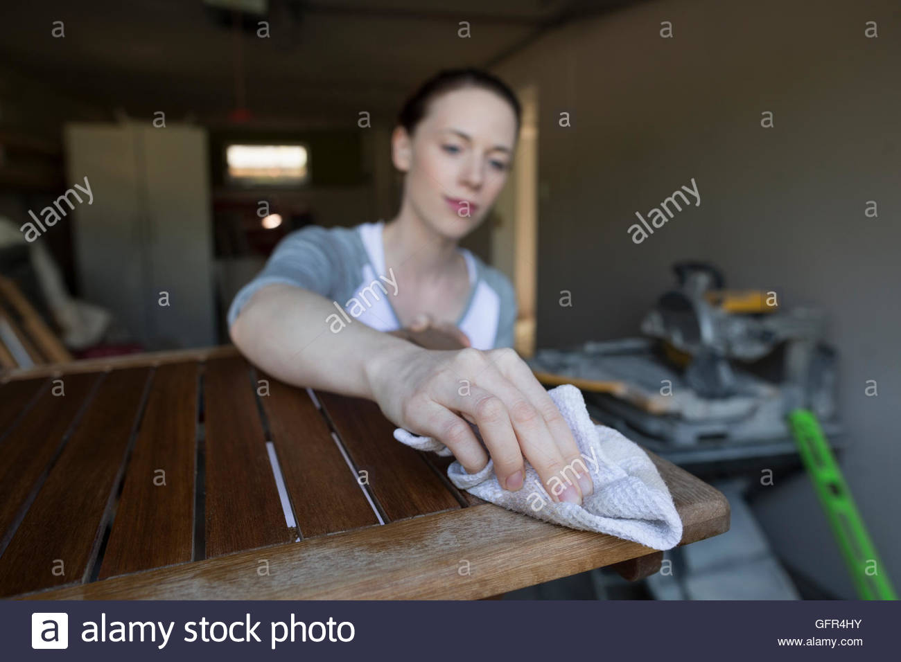 Woman staining wood furniture home improvement project in garage - Stock Image