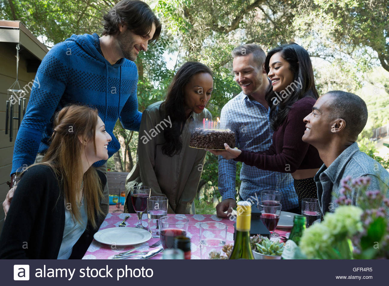 Woman blowing out birthday cake candles at patio table - Stock Image