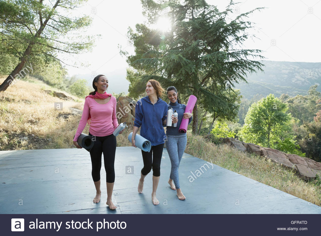 Women with yoga mats talking after class on deck - Stock Image