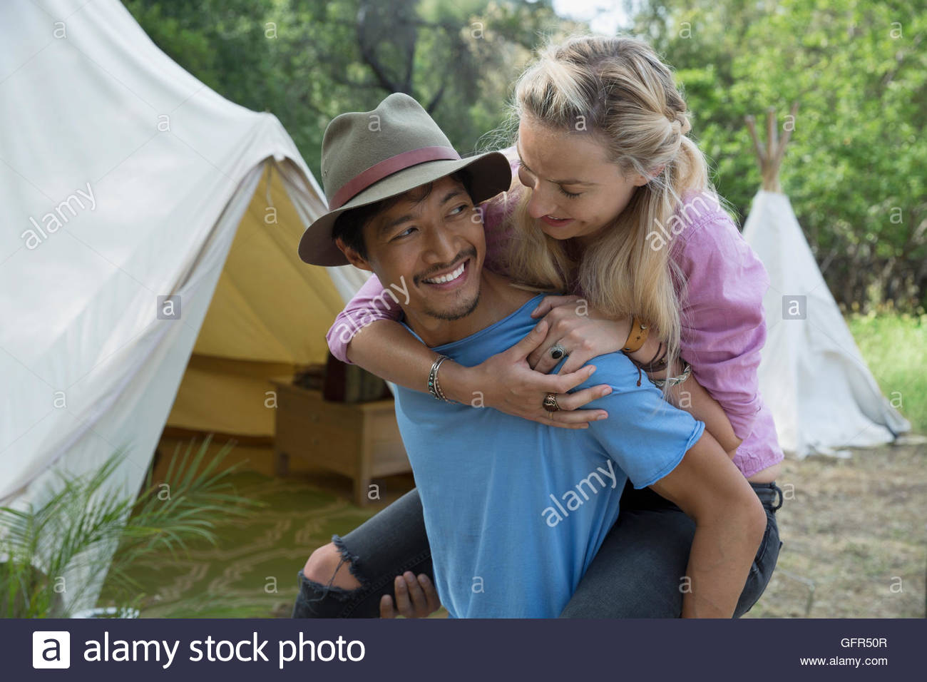 Young couple piggybacking outside camping yurt - Stock Image