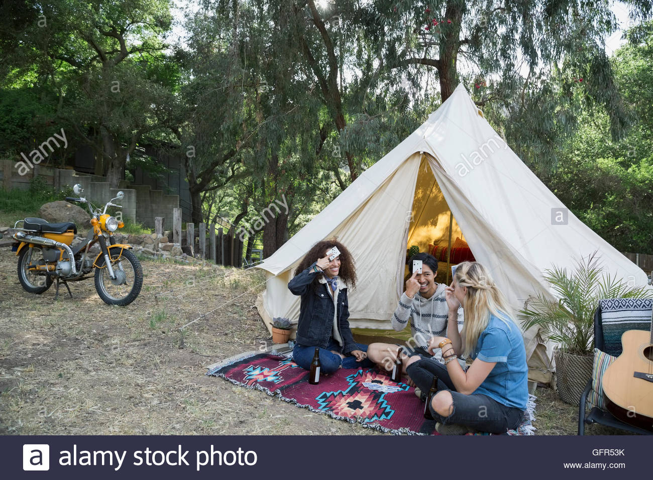 Young friends playing card game outside camping yurt - Stock Image