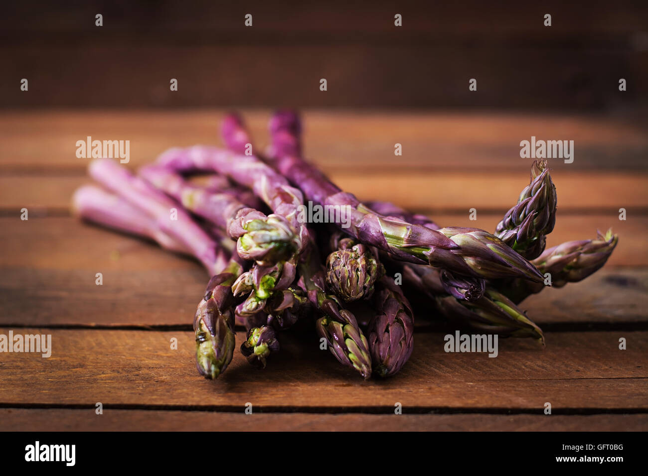 Bunch of fresh asparagus on a wooden background - Stock Image