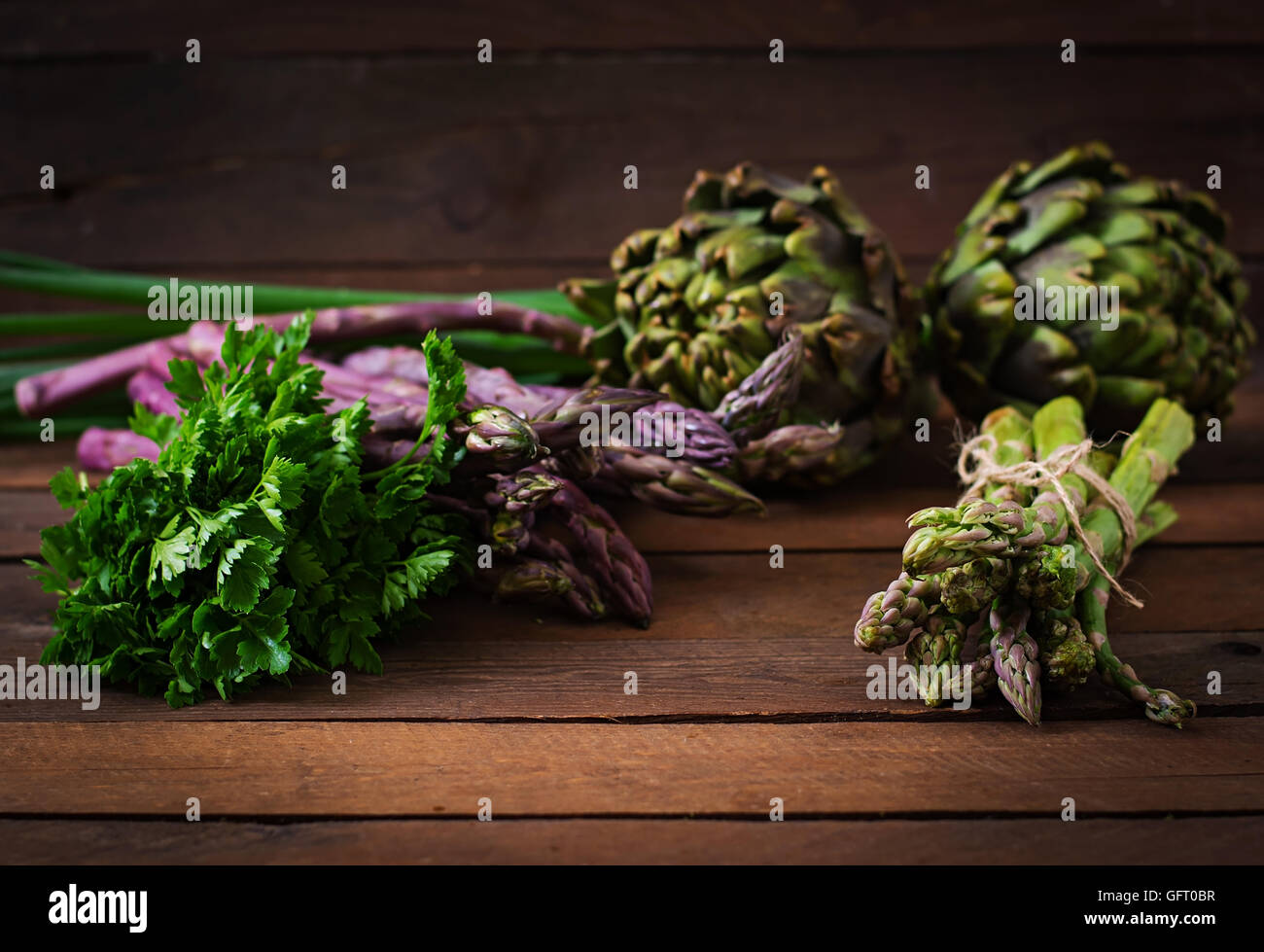 Asparagus and artichokes with herbs on a wooden background - Stock Image