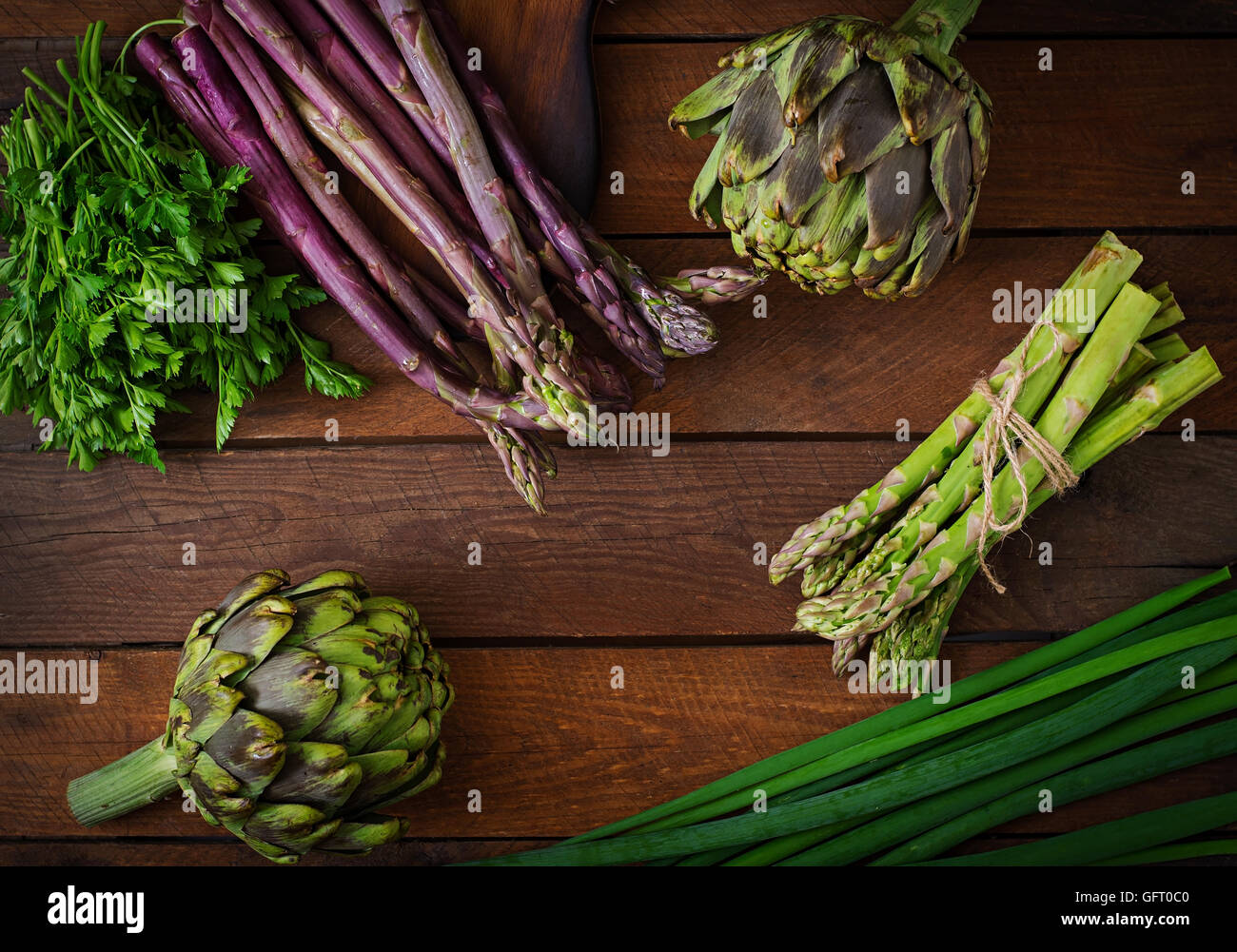 Asparagus and artichokes with herbs on a wooden background. Top view - Stock Image