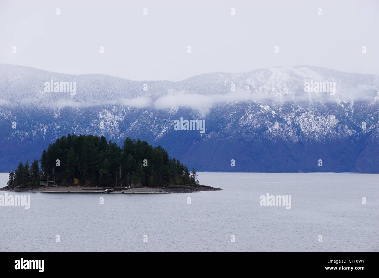 Island in Lake Pend Oreille with snow on mountains in background and low clouds - Stock Image