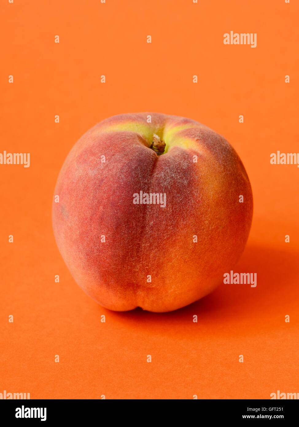 One ripe peach on orange colored background - Stock Image