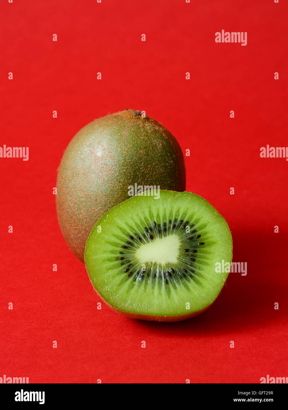 Juicy kiwi fruit on a red background - Stock Image