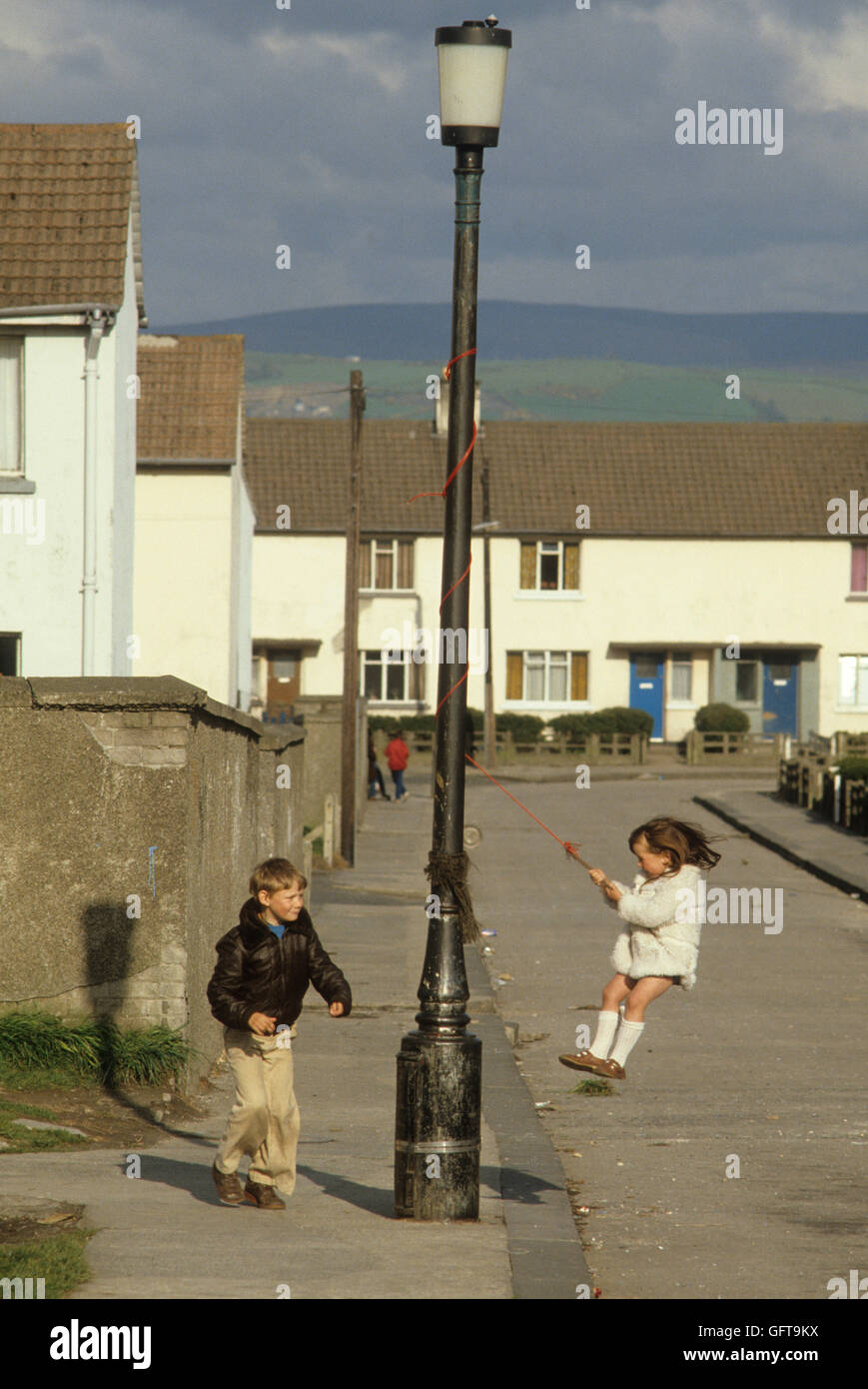 Kids Playing In Street Swinging From A Lamp Post Belfast Suburb Northern  Ireland 1980 HOMER SYKES