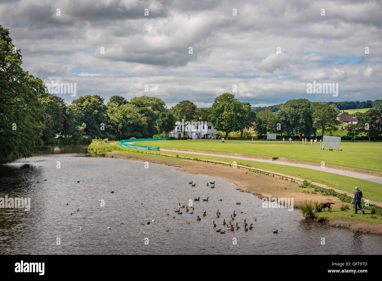 A cricket match being played at Saltaire Cricket Club in Roberts Park by the river Aire in Saltaire West Yorkshire. - Stock Image