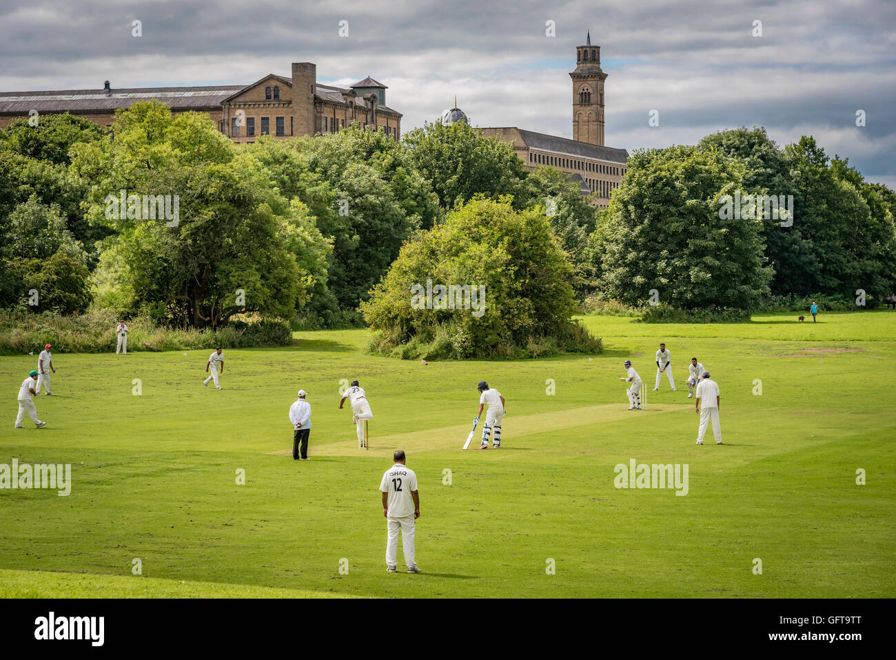 A cricket match under the New Mill at Saltaire in West Yorkshire. An NHS establishment beside the river Aire. - Stock Image