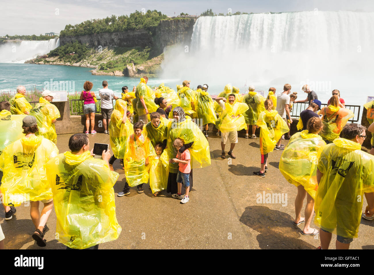 Niagara Falls, Canada - tourists on the Lower Observation Deck at the foot of the falls wearing distinctive yellow - Stock Image