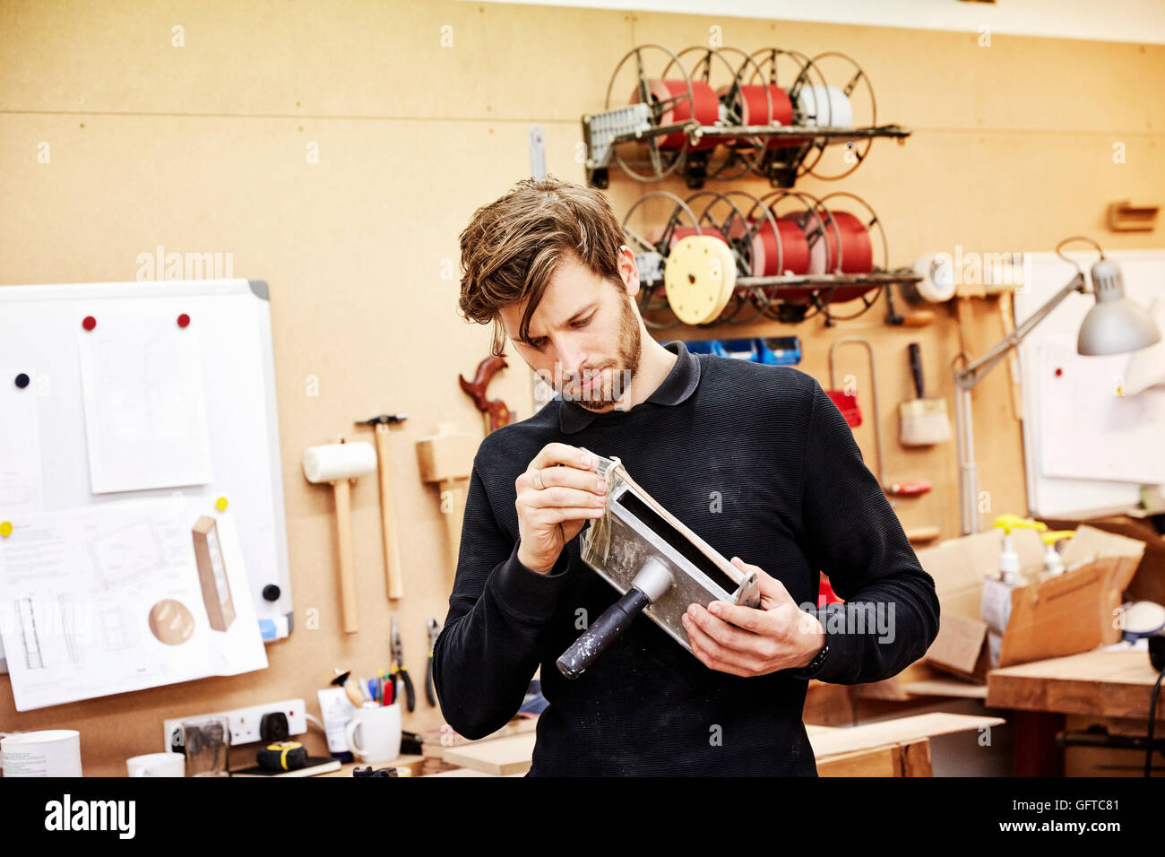 A furniture workshop  A young man holding an object and examining it closely - Stock Image