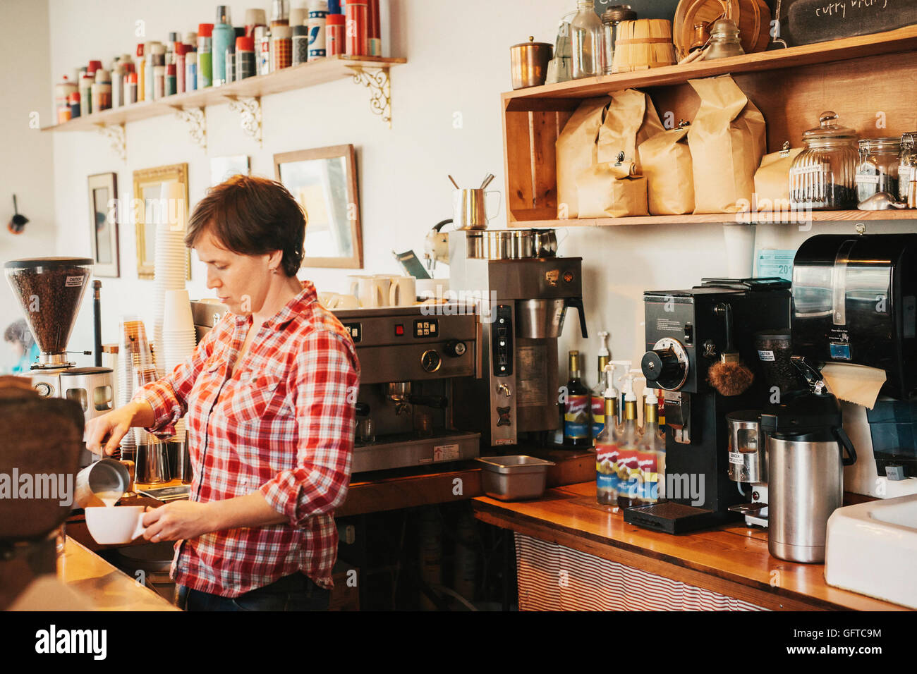 A woman in a plaid shirt working behind the counter in a coffee shop - Stock Image