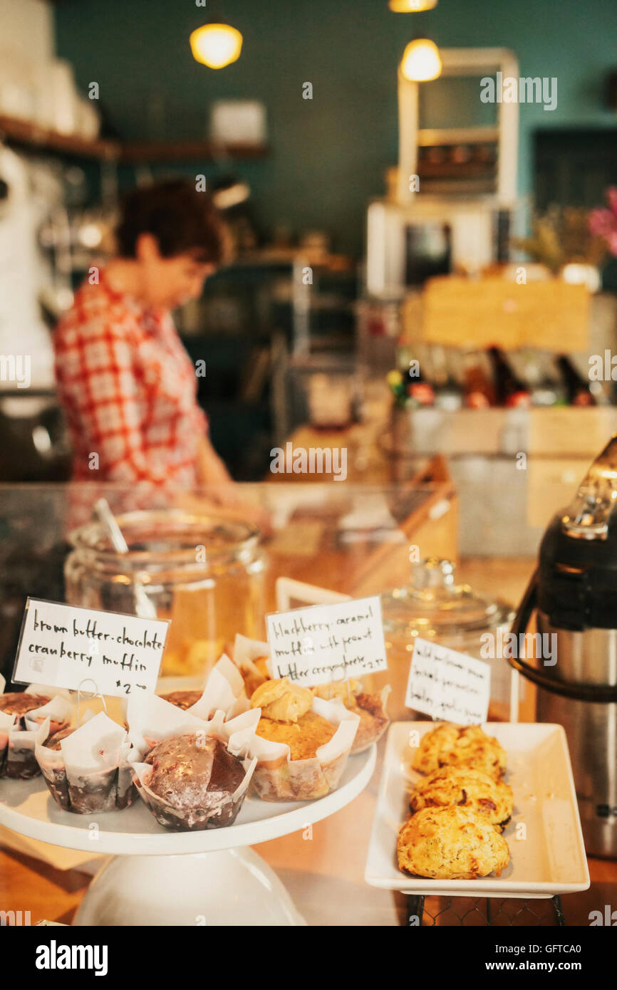 Freshly prepared food on the counter of a small coffee shop and restaurant A staff member in the background - Stock Image