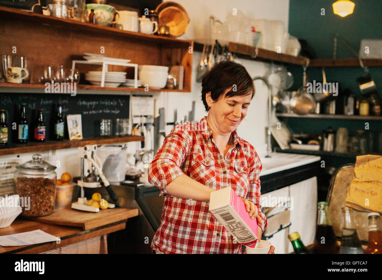 A woman working in a small commercial kitchen a coffee shop owner - Stock Image