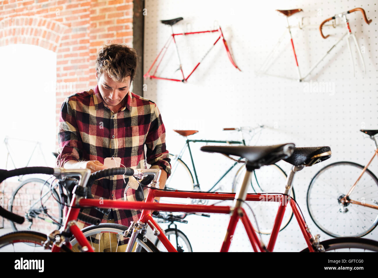 A man in a cycle shop reading the price label on a bike - Stock Image