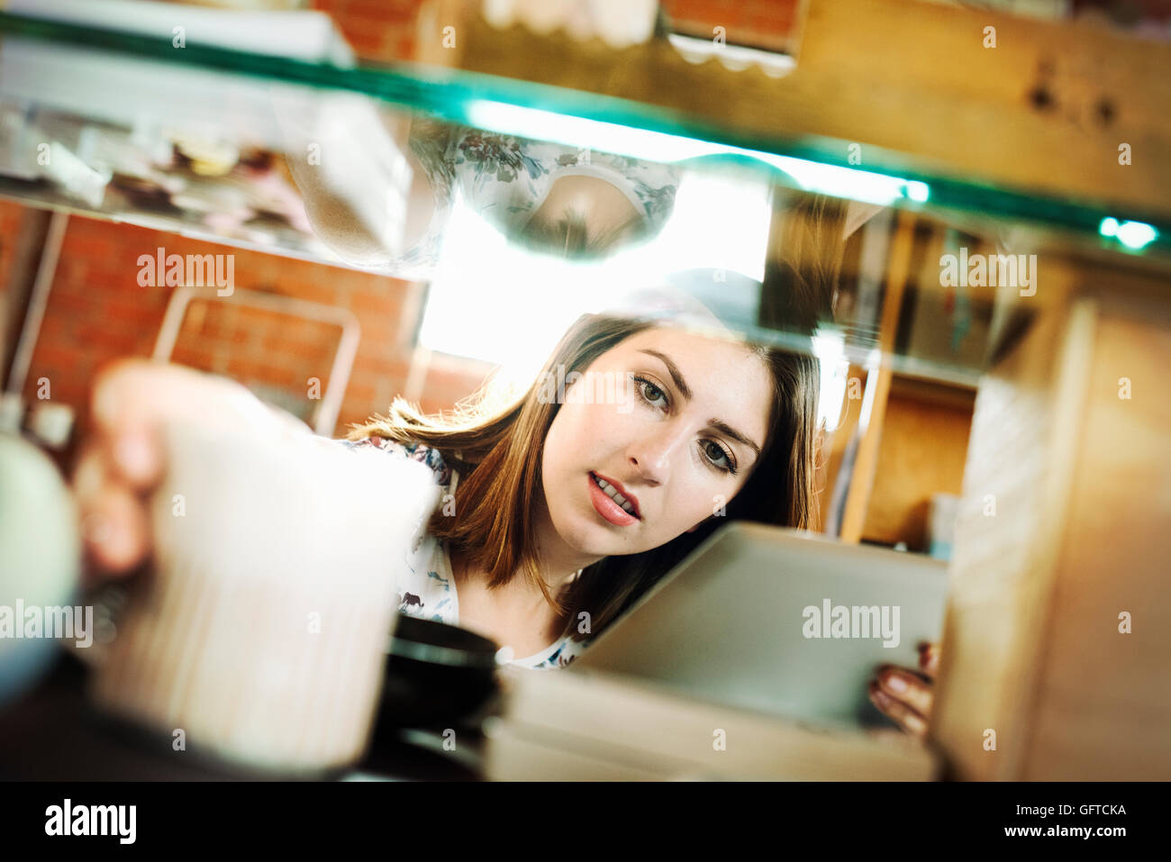 Young woman in a shop holding a digital tablet and a ceramic mug - Stock Image