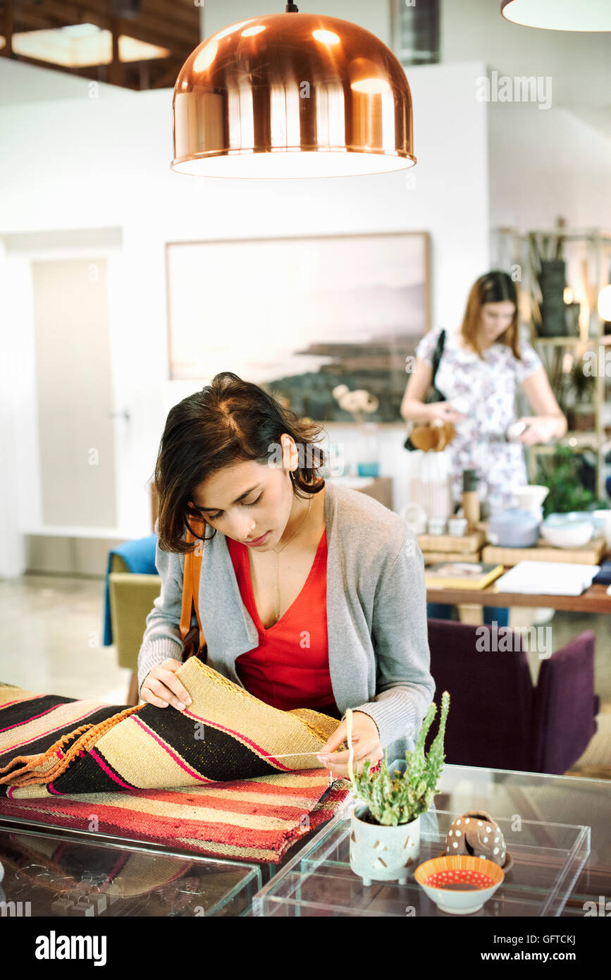 Young woman in a shop looking at small striped rugs - Stock Image