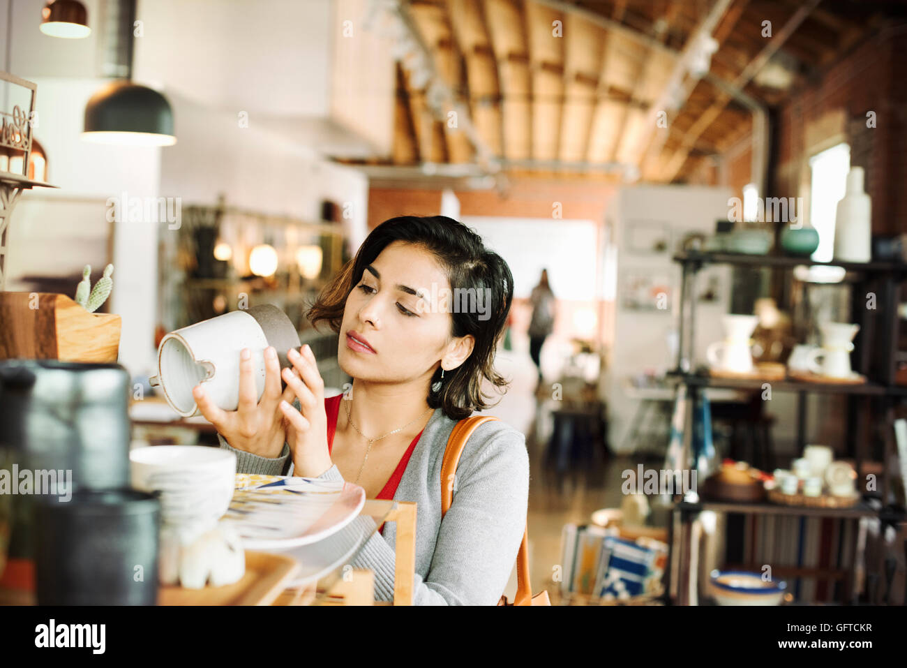 Young woman in a shop looking at a ceramic jug - Stock Image