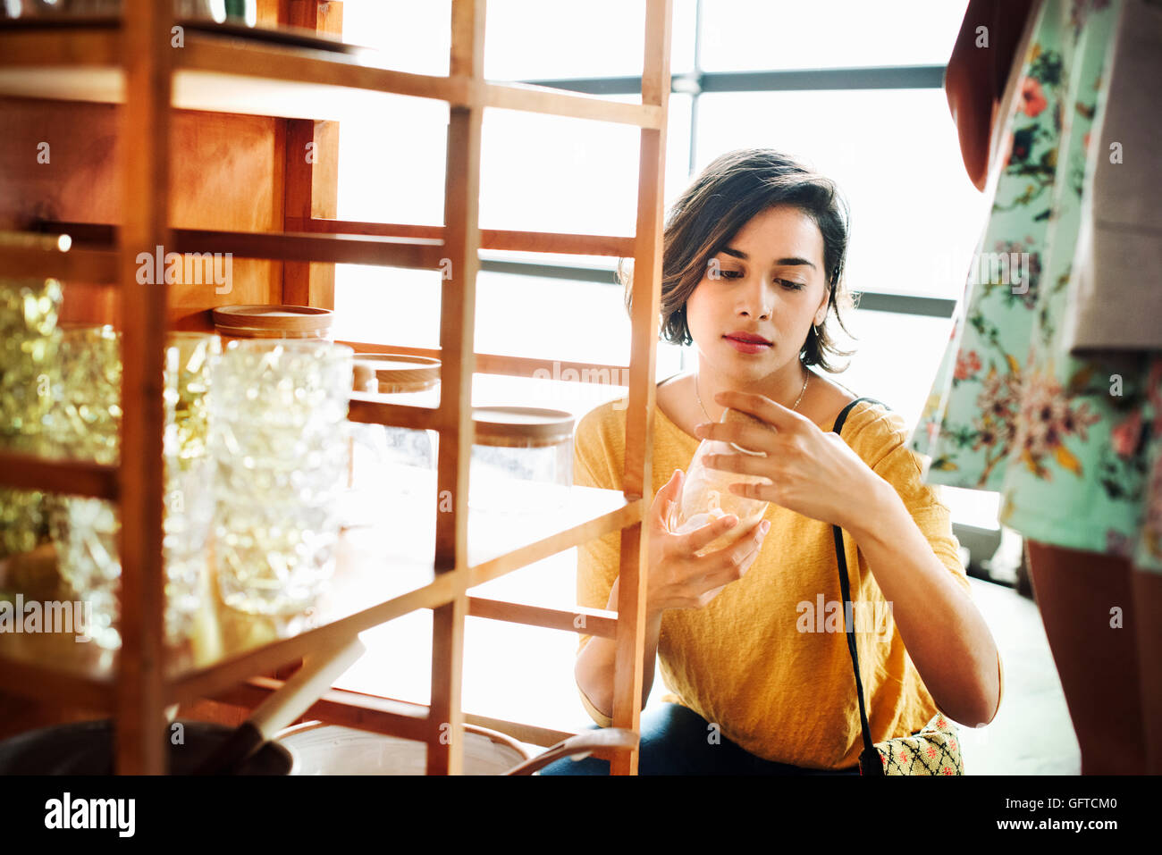 Young woman in a shop looking at a glass - Stock Image