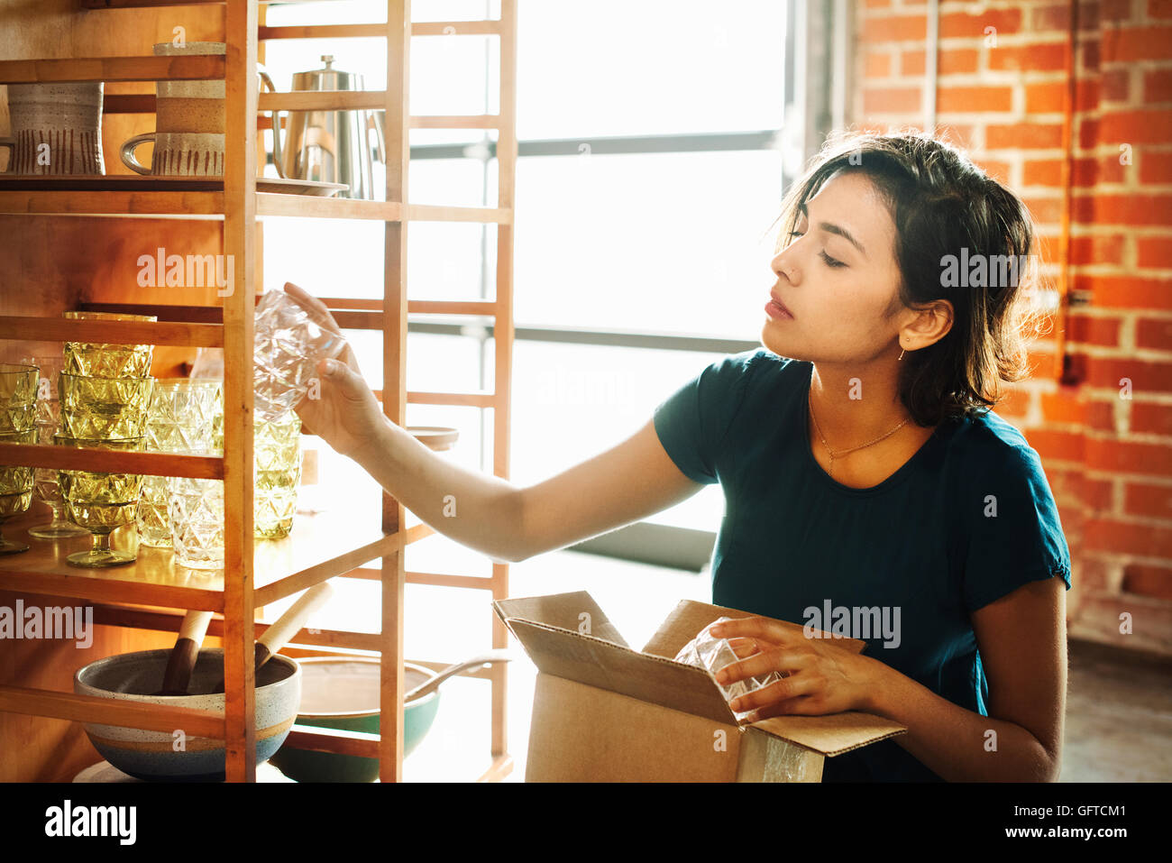 Young woman in a shop placing a drinking glass on a shelf - Stock Image