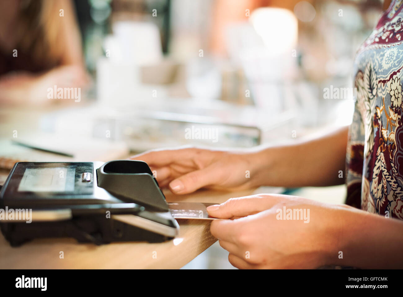 Close up of a woman using a credit card reader in a shop - Stock Image