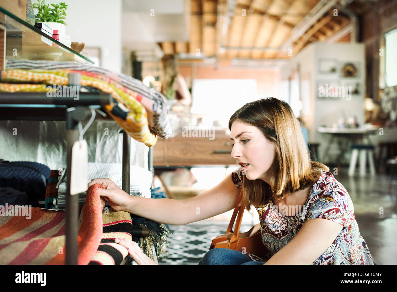 Young woman in a shop looking at rugs on a shelf - Stock Image