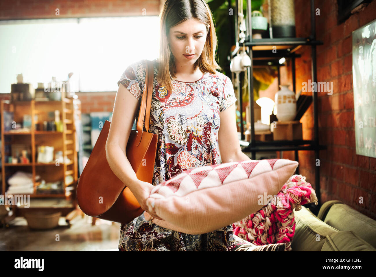 Young woman standing in a shop holding a cushion - Stock Image