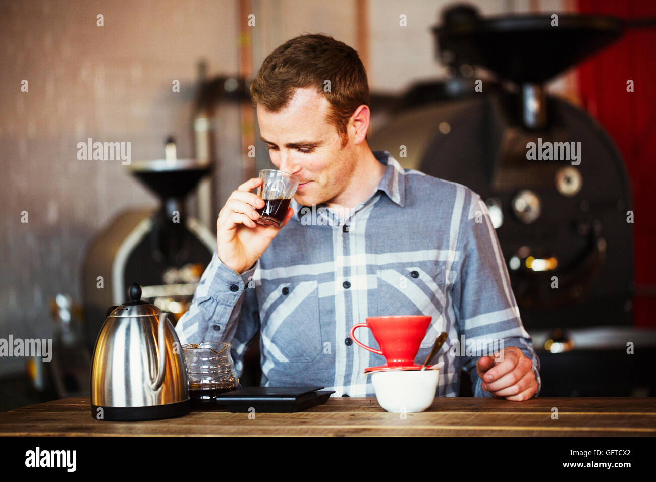 A man brewing coffee using a filter paper and drinking it - Stock Image
