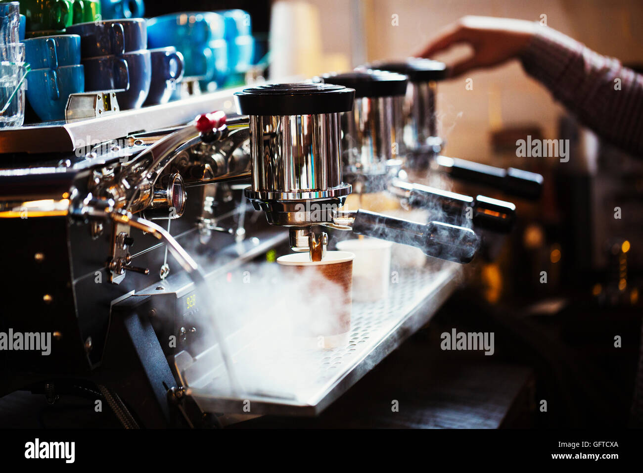 A person working at a large coffee machine with three percolating containers handles and a pipe sending out steam - Stock Image
