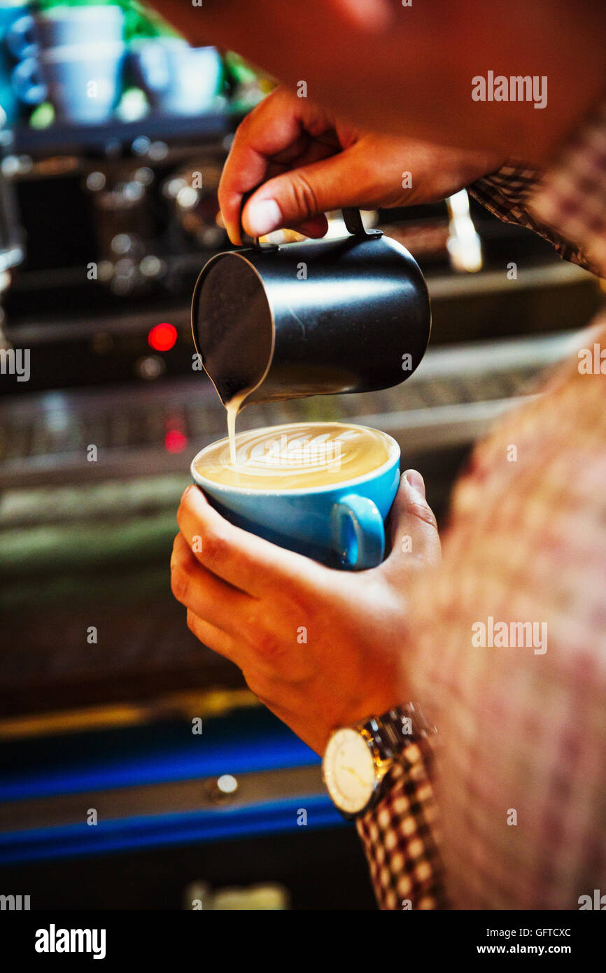 A barista pouring hot milk in to the froth on a cup of coffee to make a pattern - Stock Image