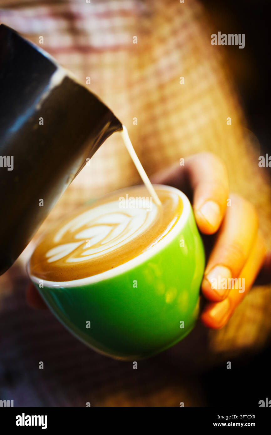 A barista creating a pattern in the froth on a cup of coffee - Stock Image