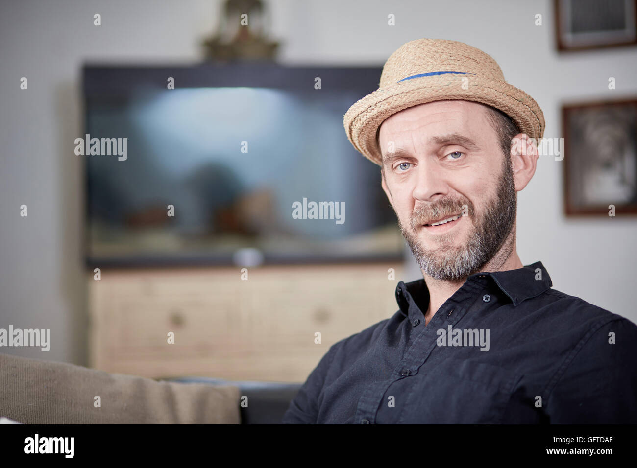 Happy man portrait sitting at home in front of aquarium - Stock Image