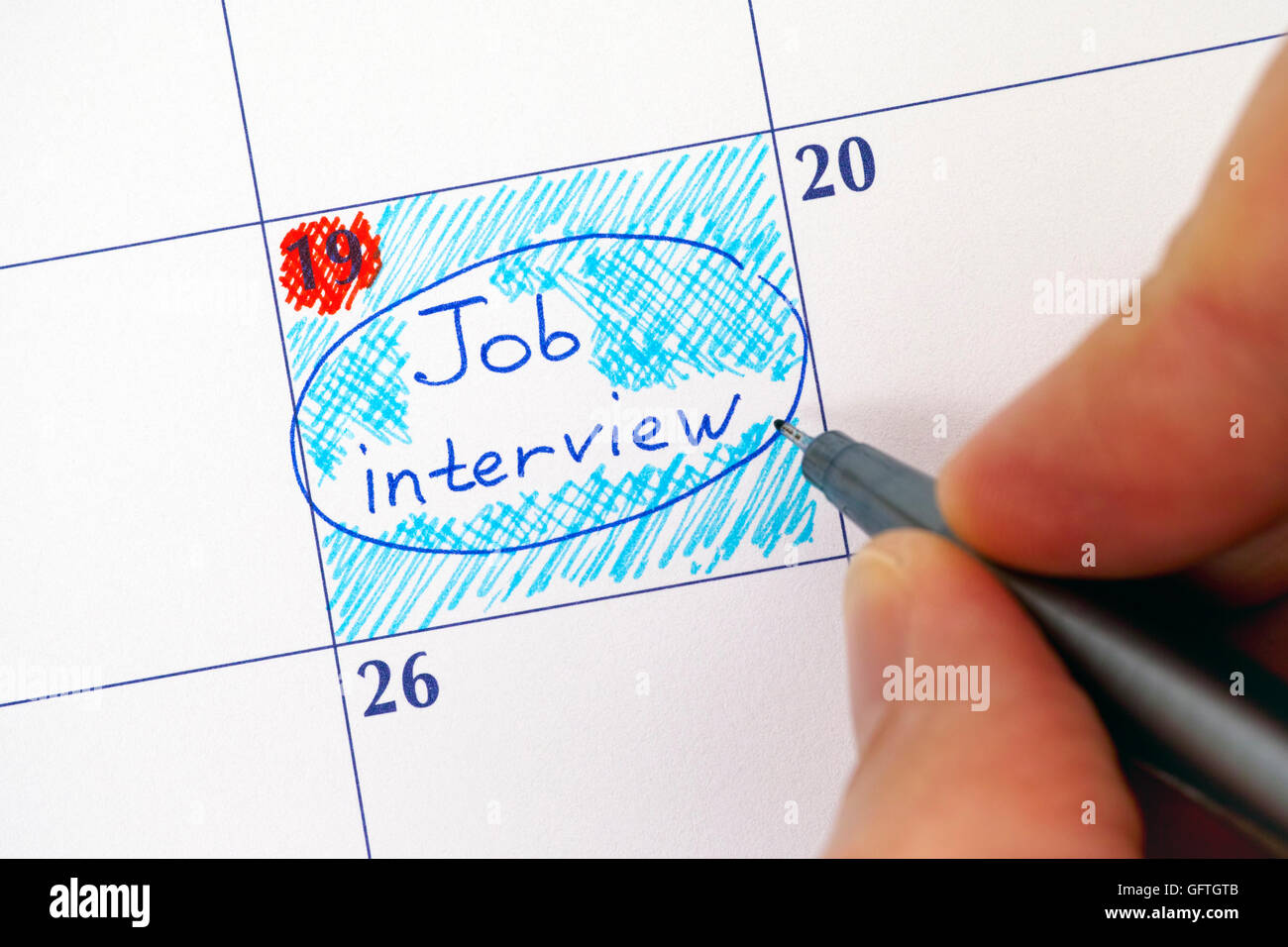 Person hand with pen writing reminder Job Interview in calendar. - Stock Image