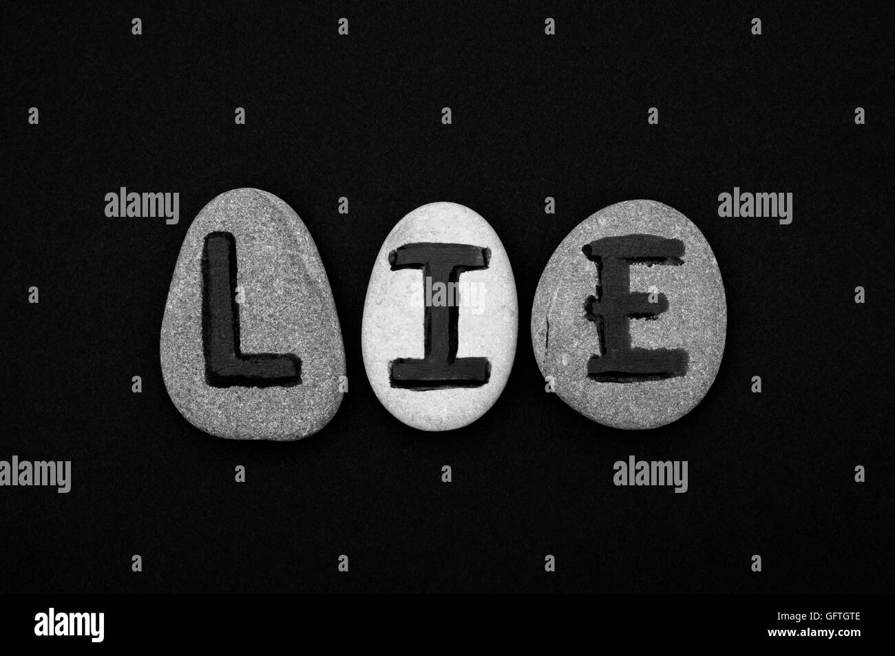 Word Lie spell out from stones with letters on black background. Black and white. Letters drawn by me. - Stock Image