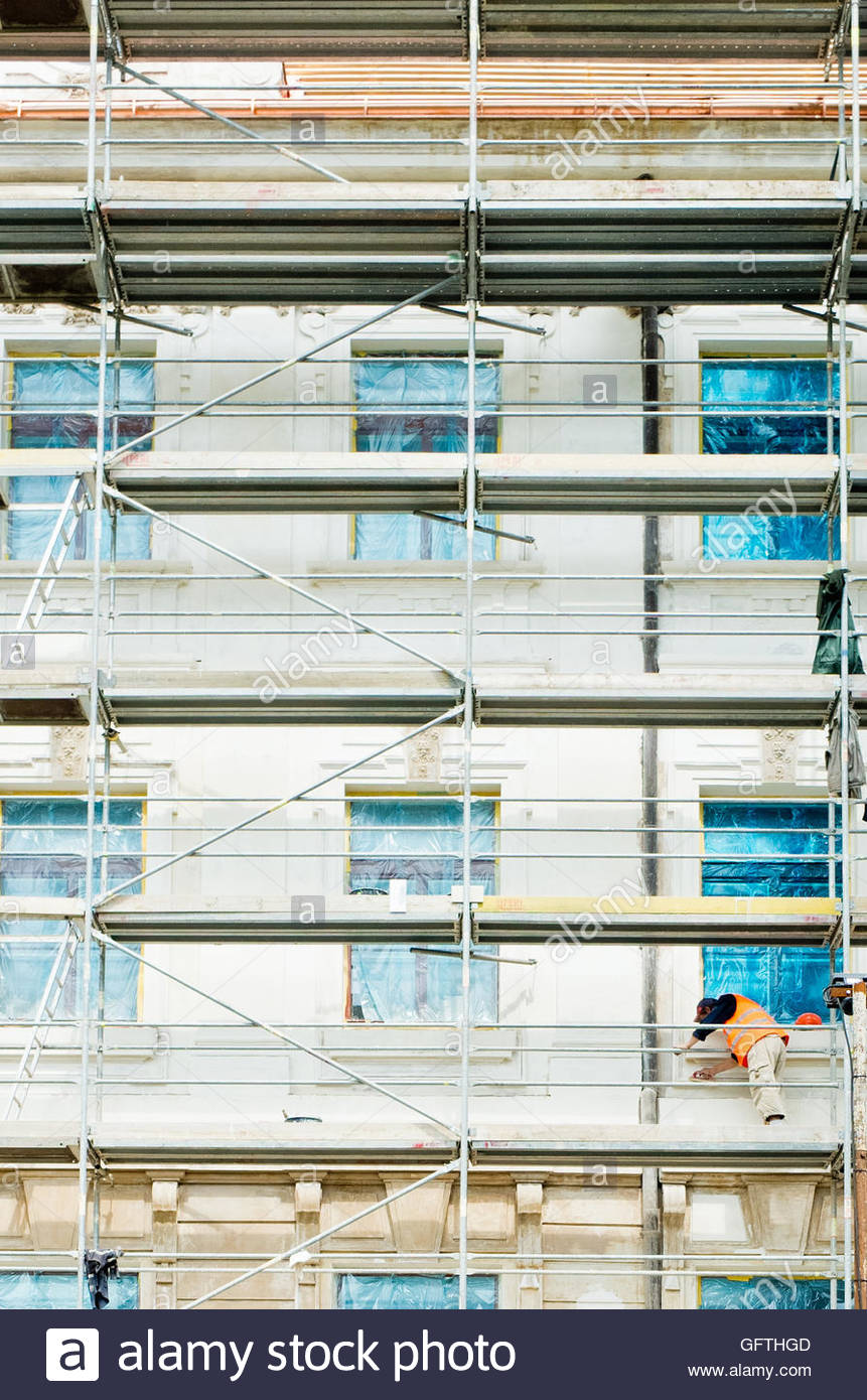 worker on scaffolds of a house in reconstruction - Stock Image