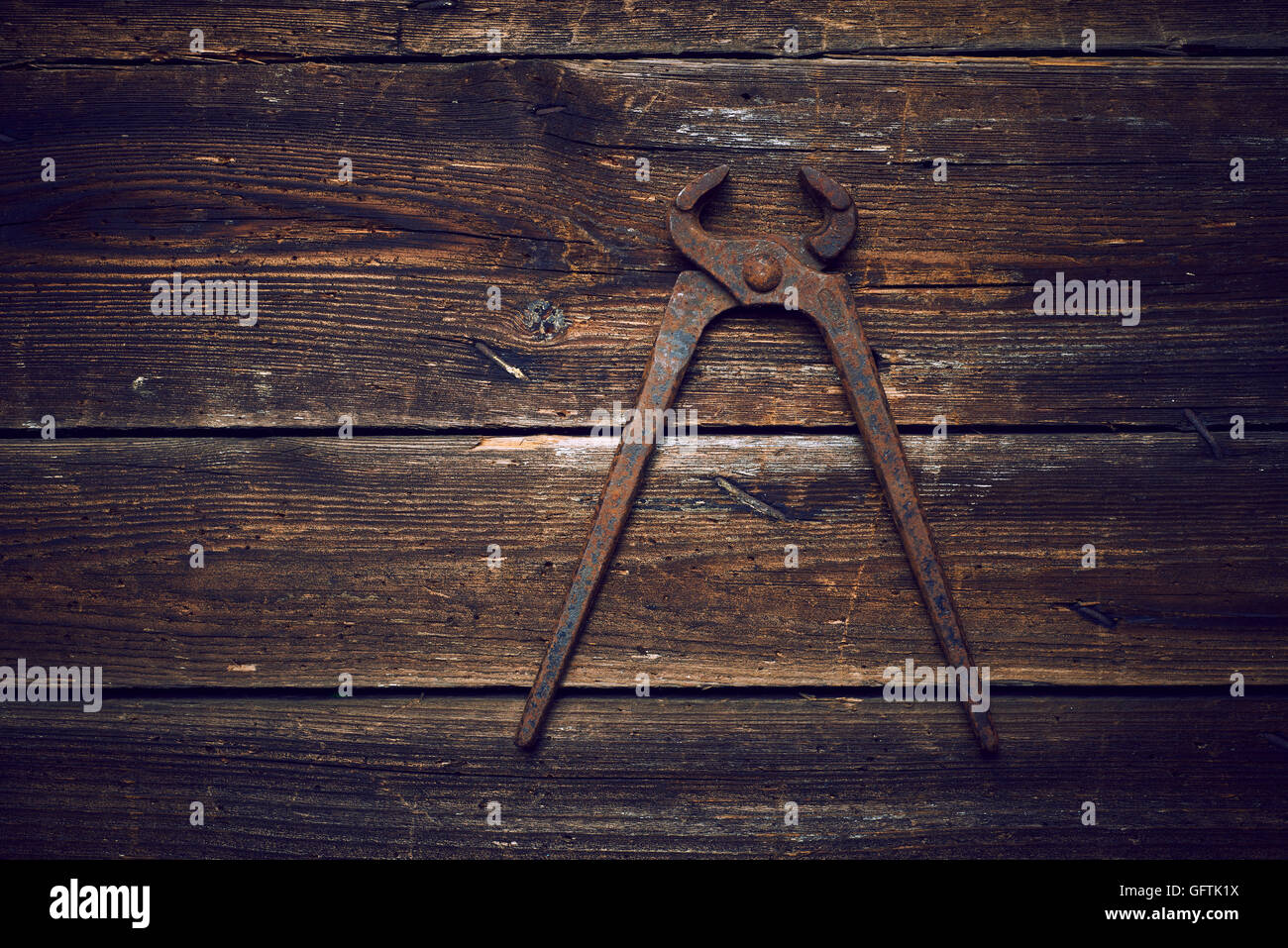Old rusty tongs with nails on wooden boards background - Stock Image