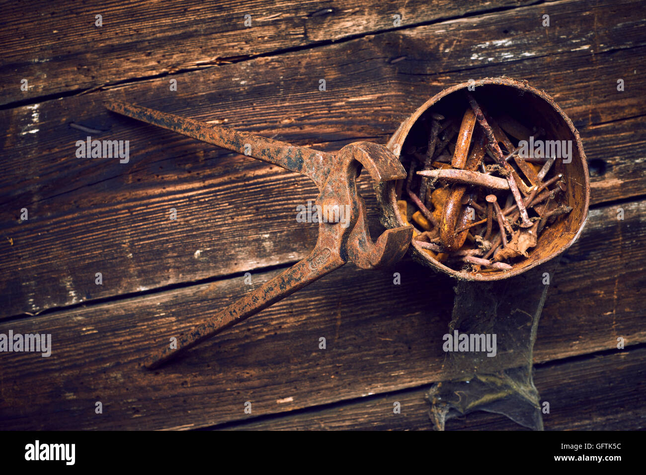old rusty pinchers with can of nails on wooden boards background - Stock Image