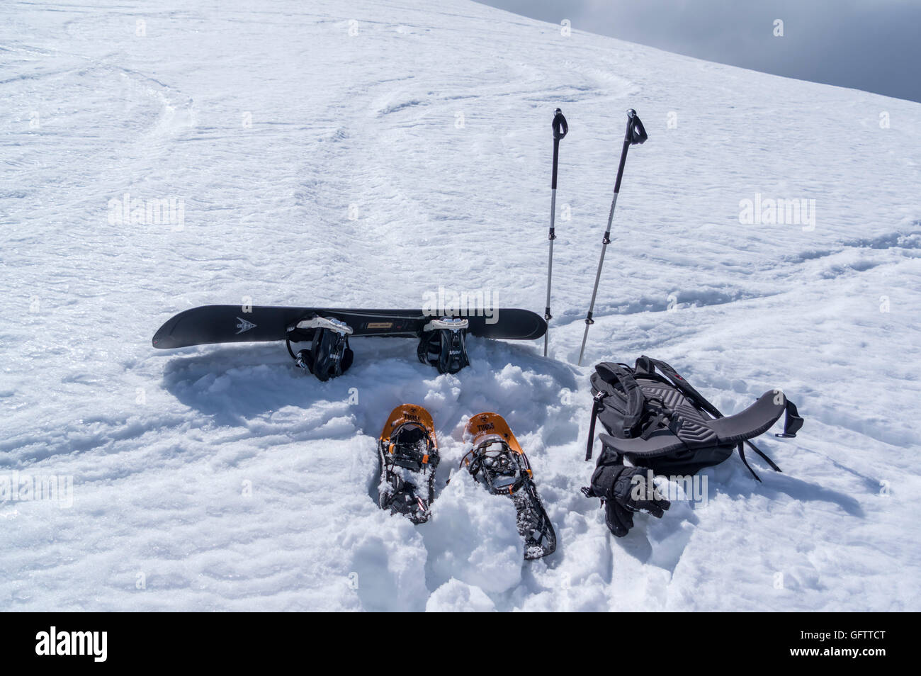 Winter backcountry gear in the snow, consisting of snowshoes and trekking poles for the ascent, and a snowboard - Stock Image