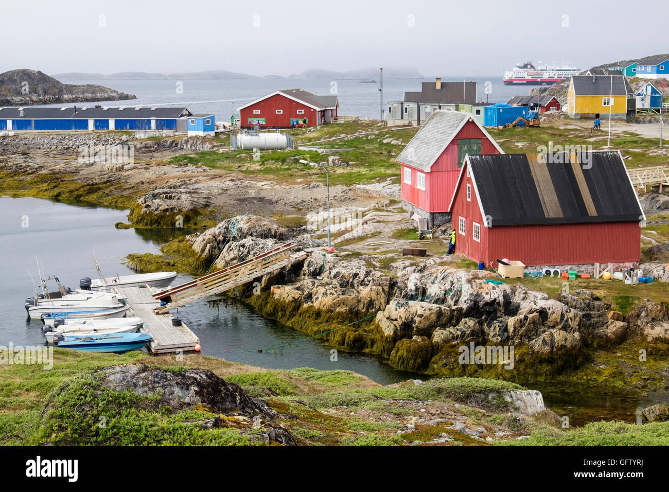 Colourful traditional buildings in small Inuit settlement with visiting cruise ship in fjord on west coast. Itilleq - Stock Image